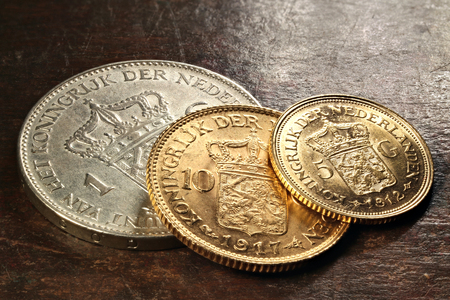 wilhelmina: Dutch silver and gold coins on rustic wooden background