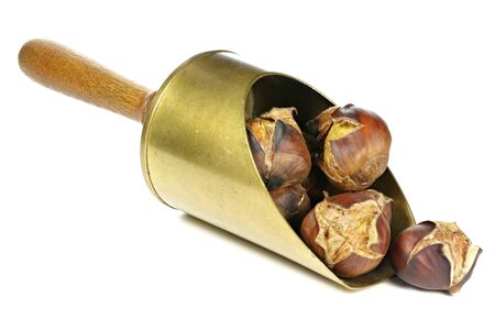 scored: roasted chestnuts in a brass scoop isolated on white background Stock Photo