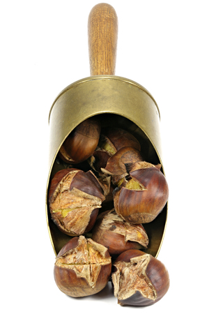 roasted chestnuts in a brass scoop isolated on white background Stock Photo