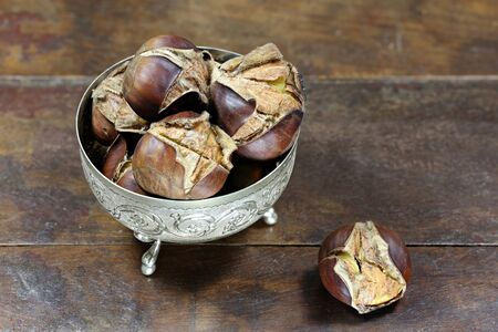 scored: roasted chestnuts in a silver bowl on rustic wooden background
