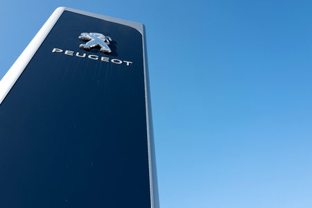 retailing: Peugeot dealership sign against blue sky