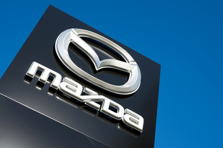 retailing: Mazda dealership sign against blue sky