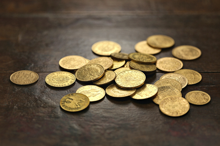 20th century: various European circulation gold coins from the 19th  20th century on rustic wooden background