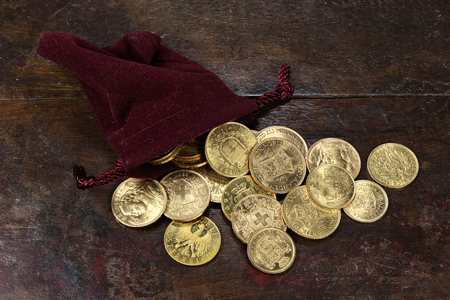 20th century: various European circulation gold coins from the 19th  20th century in a velvet purse on rustic wooden background