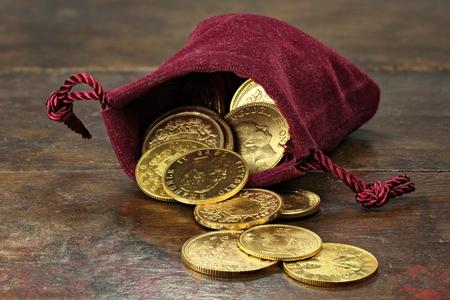 varias monedas de oro circulación europeos desde el 19 / siglo 20 en una bolsa de terciopelo en el fondo de madera rústica