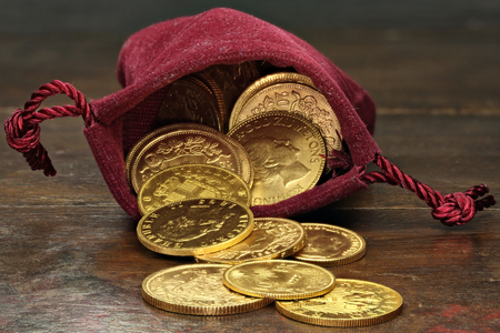 various European circulation gold coins from the 19th  20th century in a velvet purse on rustic wooden background