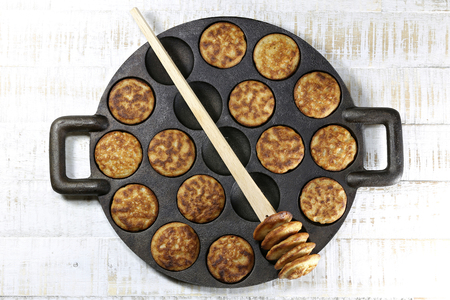 cast iron pan: homemade Dutch poffertjes in a traditional cast iron pan on wooden background