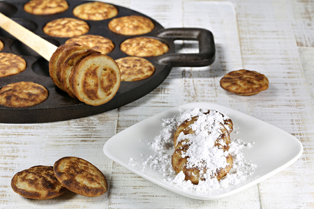 cast iron pan: homemade Dutch poffertjes baked in a traditional cast iron pan on wooden background