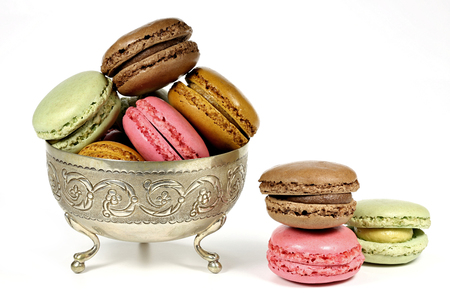 colorful macarons in a silver bowl isolated on white background
