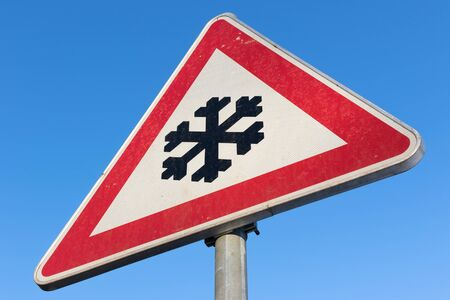 skidding: German road sign: road ahead freezes Easily and is then slippery Stock Photo