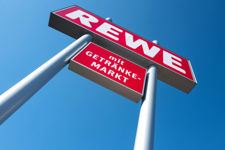 stele: REWE sign against blue sky. REWE Operates Approximately 3,300 supermarkets in Germany. Editorial
