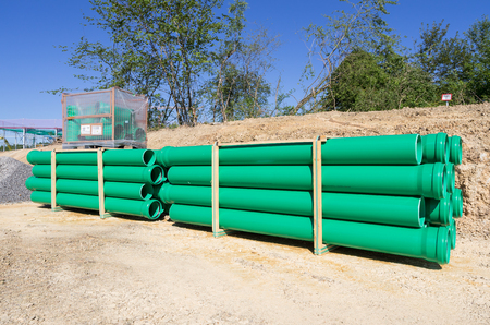 storehouse: Pallets of green sewer pipes at construction site