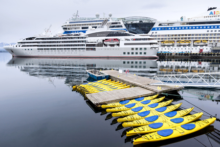le: Cruise ships and kayaks in Alesund, Norway. Alesund is noted for its concentration of Art Nouveau architecture and therefore a popular cruise destination.