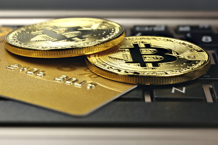 bitcoins and credit card on a laptop keyboard