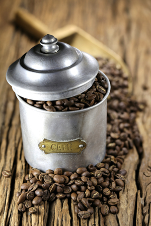 commodities: vintage French coffee can with manufacture roasted Indonesian Arabica coffee beans on rustic wooden background