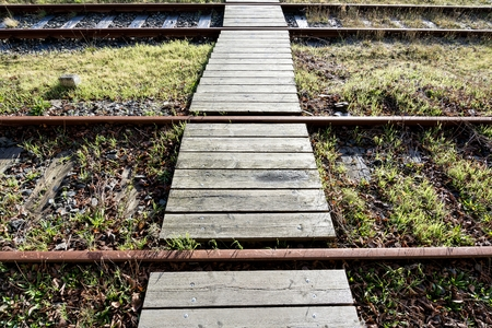 walkway over rusty rails with wooden sleepers and encroaching vegetation Stock Photo