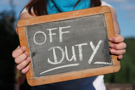 OFF DUTY written with chalk on slate shown by young female