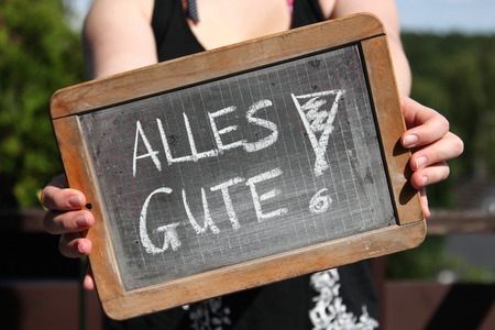 ALLES GUTE (all the best in German) written with chalk on slate shown by young female
