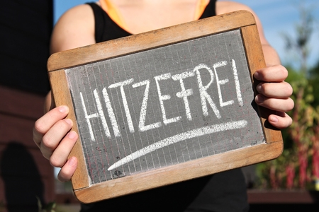 HITZEFREI (German for:  to have time off from school on account of excessively hot weather) written with chalk on slate shown by young female
