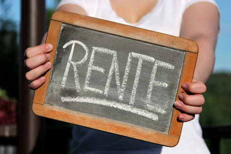 RENTE (pension in German) written with chalk on slate shown by young female Stock fotó - 92648222