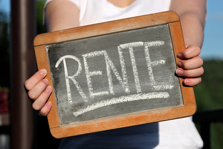 RENTE (pension in German) written with chalk on slate shown by young female