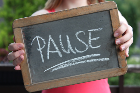 PAUSE (break in German) written with chalk on slate shown by young female