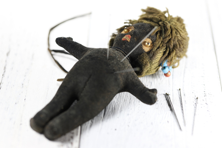vintage voodoo doll on wooden background