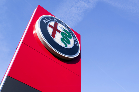 Alfa Romeo dealership sign against blue sky. The brand is known for sporty vehicles and has been involved in car racing since 1911.