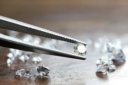 brilliant cut diamond held by tweezers Stock Photo