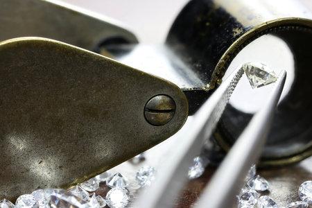 brilliant cut diamond held by tweezers Фото со стока
