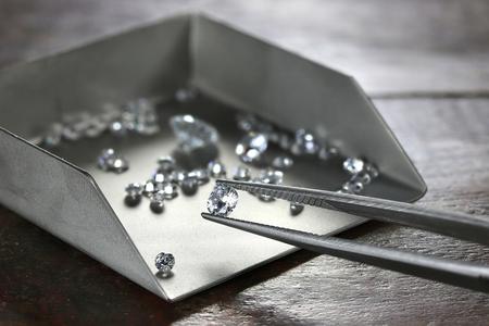 brilliant cut diamond held by tweezers 写真素材
