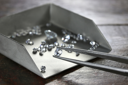 brilliant cut diamond held by tweezers 版權商用圖片