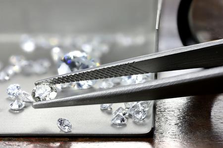 brilliant cut diamond held by tweezers Stok Fotoğraf