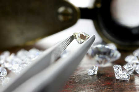 brilliant cut diamond held by tweezers Stock Photo
