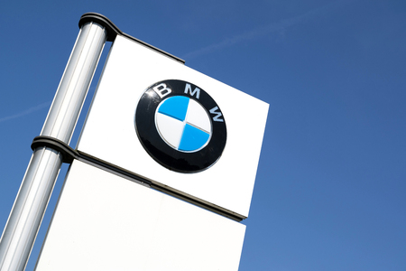 BMW dealership sign against blue sky. BMW is one of the best-selling luxury automakers in the world.