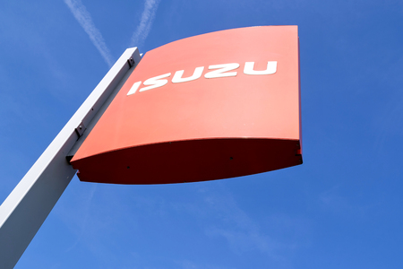 Isuzu dealership sign against blue sky. Isuzu is a Japanese commercial vehicles and diesel engine manufacturing company headquartered in Tokyo.