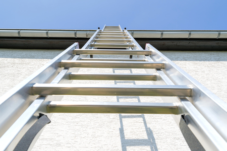 three section aluminum ladder leaning against house Stock Photo - 102383425