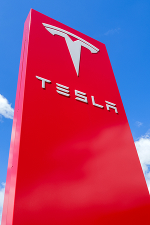 Tesla dealership sign against blue sky. Tesla is an American multinational corporation that specializes in electric vehicles, energy storage and solar panel manufacturing.