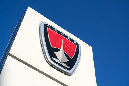 Rover dealership sign against blue sky.