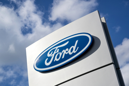 Ford dealership sign against blue sky. Ford is the second-largest U.S.-based automaker.
