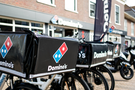 Delivery bikes of Domino's restaurant. Domino's is an American pizza restaurant chain founded in 1960.