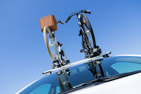 bicycle rack on top of white car