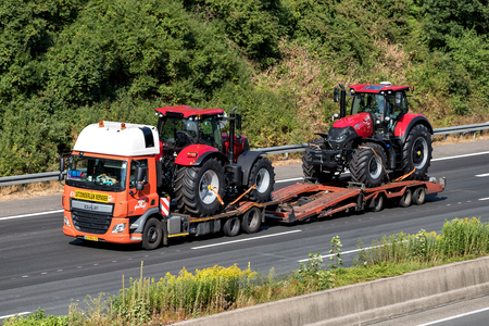 Flatbed truck with two farm tractors on motorway.