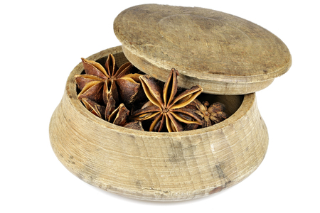 star anise in a vintage wooden bowl isolated on white background