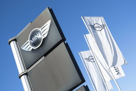 Mini dealership sign against blue sky. Mini is a British automotive marque, owned by BMW since 2000, and used by them for a range of small cars.