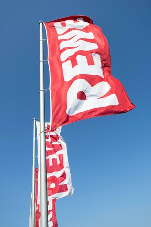 REWE flags against blue sky. REWE operates approximately 3,300 supermarkets in Germany. Sajtókép