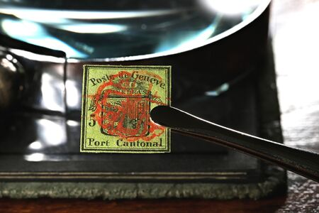 5 cent Geneva cantonal stamp from 1847 held by tweezers. Фото со стока