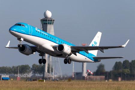 Dutch KLM Cityhopper Embraer ERJ-190 with registration PH-EZI taking off runway 36L (Polderbaan) of Amsterdam Airport Schiphol. Editorial