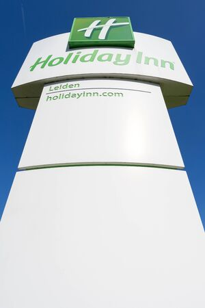 Holiday Inn Hotel sign against blue sky. Holiday Inn is a British-owned American brand of hotels, and a subsidiary of InterContinental Hotels Group.