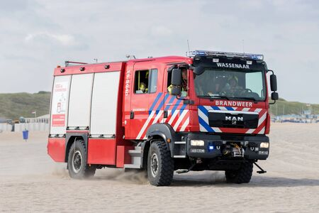 Dutch MAN TGM fire engine with active blue emergency lighting on the beach